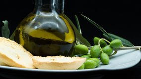 Some olives and a jar full of oil and a branch of olive tree on. A white dish on a black background stock images