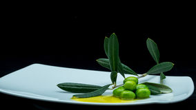 Some olives and oil. On a white dish on a black background Royalty Free Stock Photos