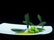 Some olives and oil. On a white dish on a black background Stock Photo