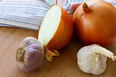 Some onion and garlic on board. Some onion and garlic on wooden board royalty free stock photos