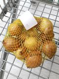 Some onions isolated in bag. On a Cart in a supermarket Royalty Free Stock Photos