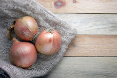 Some onions on a sack on a wooden table Stock Photos
