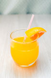 Some orange juice with straw into glass for breakfast. Very healthy orange cocktail with straw into glass for breakfast Stock Photos