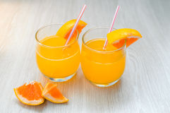 Some orange juice with straw into glass for breakfast. Very healthy orange cocktail with straw into glass for breakfast Stock Image