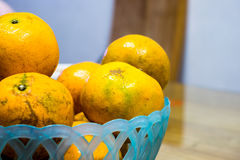 Some oranges in a blue basket. Over a wooden Stock Image