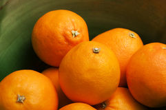 Some oranges fruits in a green bowl. Some oranges fruits in a green earthenware bowl stock photography