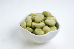 Some organic broad beans. In a white bowl Stock Images