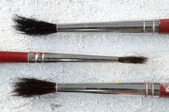 Some paint brushes on a white wooden table Royalty Free Stock Photo