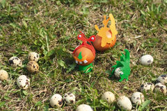 Some painted Easter eggs on the lawn. Joke photo with chicken and quail eggs, some of them decorated with cloth and toy eyes. Day light, shot on the green lawn Royalty Free Stock Photos