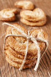 Some palmeras, spanish palmier pastries. Tied with a string on a rustic wooden table Royalty Free Stock Photography