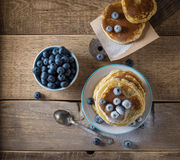 Some pancakes with blueberry on the wood table. Morning rustic mood Stock Image
