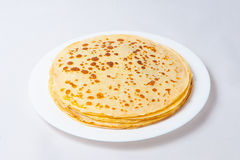 Some pancakes on the white plate. Some roasted pancakes on the white plate on white background Stock Image