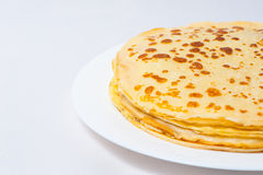 Some pancakes on the white plate. Some roasted pancakes on the white plate on white background Royalty Free Stock Images