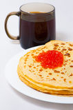 Some pancakes on the white plate. Some roasted pancakes on the white plate on white background with cup Stock Photography