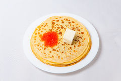 Some pancakes on the white plate. Some roasted pancakes on the white plate on white background with caviar and butter Royalty Free Stock Photography