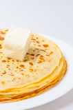 Some pancakes on the white plate. Some roasted pancakes on the white plate on white background with  butter Royalty Free Stock Image