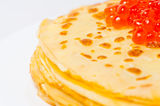 Some pancakes on the white plate. Some roasted pancakes on the white plate on white background with caviar Royalty Free Stock Photography