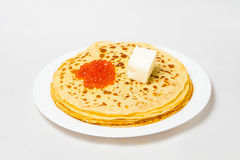 Some pancakes on the white plate with red caviar. Some roasted pancakes on the white plate on white background Royalty Free Stock Images