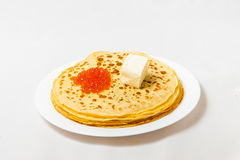 Some pancakes on the white plate with red caviar. Some roasted pancakes on the white plate on white background Stock Photo