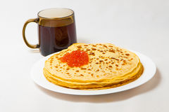 Some pancakes on the white plate with red caviar. Some roasted pancakes on the white plate on white background Royalty Free Stock Photos