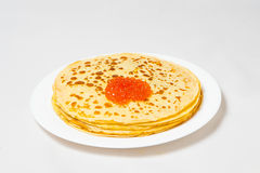 Some pancakes on the white plate with red caviar. Some roasted pancakes on the white plate on white background Stock Images