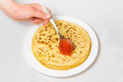 Some pancakes on the white plate with red caviar. Some roasted pancakes on the white plate on white background Stock Image