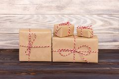 Some paper parcels christmas gift boxes wrapped with paper kraft and tied with red white baker twine in a dark wooden table. Chris. Tmas gift boxes royalty free stock photos