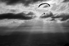 Some para-gliders and hang-gliders flying over a valley, with di. Stant mountains and hills and sun rays coming out through the clouds royalty free stock image