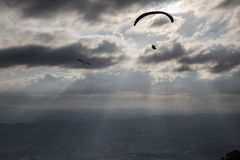 Some para-gliders and hang-gliders flying over a valley, with di. Stant mountains and hills and sun rays coming out through the clouds royalty free stock photography