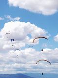 Some paragliders on a background of blue cloudy sky.  Stock Photo