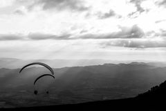 Some paragliders flying over a mountain scenery, with some faint sunrays in the background.  royalty free stock photography