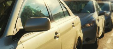 Some parked cars with the sun shining on them. Some parked cars with the sun shining on it with selective focus on the back of the rear-view mirror, shallow Royalty Free Stock Images