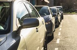 Some parked cars with the sun shining on them. Some parked cars with the sun shining on it with selective focus on the back of the rear-view mirror, shallow Royalty Free Stock Image
