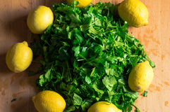 Some parsley and a circle of lemons Stock Photos