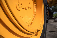 Some parts from a large car for transportation of ore called Bel. Some parts from a large yellow car for transportation of ore called Belaz, black wheels, blue royalty free stock photography