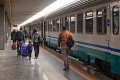 Some passengers are going to take the train departing. Naples, Italy - March 13, 2017: In the central railway station passengers make their way to the train stock images
