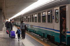 Some passengers are going to take the train departing. Naples, Italy - March 13, 2017: In the Naples central station in a family of mother, father and little son Stock Photography