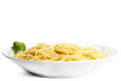 Some pasta on a plate with basil. On white background royalty free stock photos