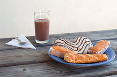 Some pastries in a plate and a chocolate milk glass for breackfast. Some pastries in a plate and a chocolate milk glass for outdoor breackfast stock photo