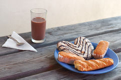 Some pastries in a plate and a chocolate milk glass for breackfast. Some pastries in a plate and a chocolate milk glass for outdoor breackfast royalty free stock photo