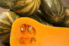 Some Paulistan pumpkins in a basket over a wooden. Some Paulistan pumpkins in a basket over a wooden surface on a pumpkin plantation background. Fresh vegetable Stock Photos