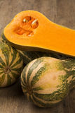 Some Paulistan pumpkins in a basket over a wooden. Some Paulistan pumpkins in a basket over a wooden surface on a pumpkin plantation background. Fresh vegetable Stock Images