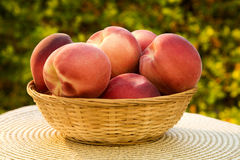 Some peaches in a basket over a wooden surface. Fresh fruits Royalty Free Stock Photo