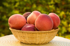 Some peaches in a basket over a wooden surface. Fresh fruits Royalty Free Stock Photography