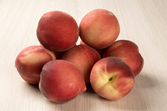 Some peaches in a basket over a wooden surface. Fresh fruits Royalty Free Stock Images