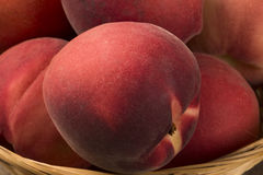 Some peaches in a basket over a wooden surface. Fresh fruits Royalty Free Stock Image