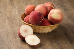 Some peaches in a basket over a wooden surface. Fresh fruits Stock Photo
