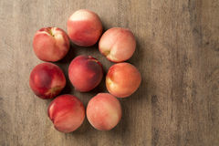 Some peaches in a basket over a wooden surface. Fresh fruits Stock Photos