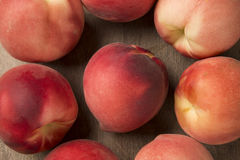 Some peaches in a basket over a wooden surface. Fresh fruits Stock Images