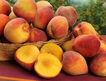 Some peaches in a basket over a wooden surface. Fresh fruits Royalty Free Stock Photos